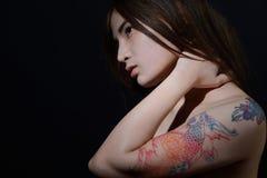 Belle femme asiatique avec un tatouage sur son bras et épaule, foncés image libre de droits