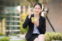 Belle femme asiatique d'affaires mangeant de la salade sur le banc de parc image stock