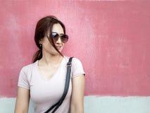 Belle femme asiatique dans des lunettes de soleil dans une ville au-dessus de fond rose de mur photos libres de droits