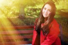 Belle femme asiatique dans le manteau rouge Photographie stock