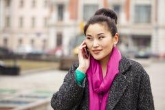 Belle femme asiatique heureuse appelant par le téléphone sur le stree de ressort Photos stock