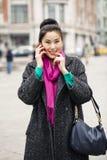 Belle femme asiatique heureuse appelant par le téléphone sur le stree de ressort Images stock