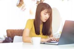 Belle femme asiatique heureuse travaillant sur un ordinateur portable se reposant sur la table dans la maison Matin elle habillen images libres de droits