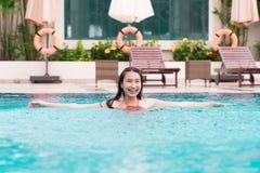 Belle femme asiatique souriant dans une piscine image stock