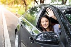Belle femme asiatique souriant et appréciant conduire une voiture sur la route image stock