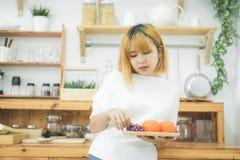 Belle femme asiatique tenant des fruits et légumes dans la cuisine à sa maison photos stock