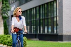 belle femme attirante s'asseyant sur le vélo sur la rue photographie stock