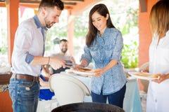 Belle femme au barbecue avec des amis Images libres de droits