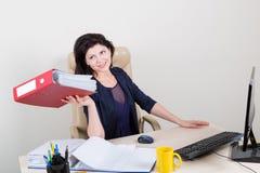 Belle femme au bureau donnant le dossier Image stock