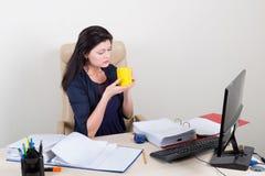 Belle femme au bureau tenant la tasse Photographie stock libre de droits