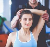 Belle femme au gymnase s'exerçant avec son entraîneur photo stock