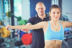 Belle femme au gymnase s'exerçant avec son entraîneur Beau femme Gymnastique Images libres de droits