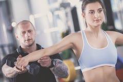 Belle femme au gymnase s'exerçant avec son entraîneur Beau femme Gymnastique photographie stock libre de droits