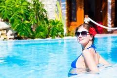 Belle femme aux cheveux longs dans la piscine de luxe Photo stock