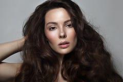 Belle femme avec de longs cheveux bouclés et maquillage propre Image stock