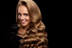 Belle femme avec de longs cheveux bouclés onduleux blonds brillants beauté Photo libre de droits