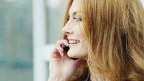 Belle femme avec de longs cheveux, parlant au téléphone dehors banque de vidéos
