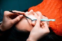 Belle femme avec de longs cils dans un salon de beauté Procédure d'extension de cil Les mèches se ferment  image libre de droits
