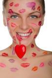 Belle femme avec des baisers sur le visage tenant le coeur dans des dents Photos libres de droits