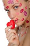 Belle femme avec des baisers sur le visage tenant le coeur dans la bouche Image stock