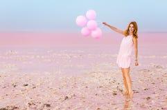 Belle femme avec des baloons sur le lac de sel rose image libre de droits