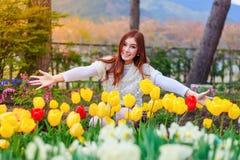 Belle femme avec des fleurs de tulipes dans le jardin photo stock