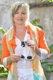 Belle femme avec des jumelles et des verres de soleil Photographie stock