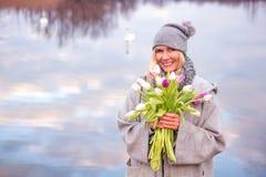 Belle femme avec des tulipes devant le lac photographie stock