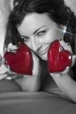 Belle femme avec deux coeurs et boucle d'oreille miroitante Photo stock