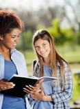 Belle femme avec l'ami tenant le livre dans le campus Images libres de droits
