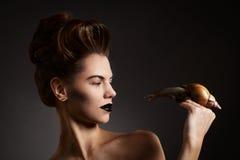 Belle femme avec l'escargot avec des yeux au beurre noir et des lèvres. Mode. Allez Photographie stock libre de droits