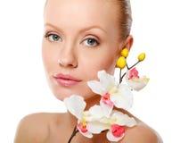 Belle femme avec l'orchidée au-dessus du fond blanc Photo stock