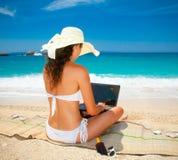 Belle femme avec l'ordinateur portable sur la plage La Grèce Image libre de droits