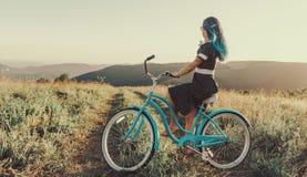 Belle femme avec la bicyclette de croiseur Photographie stock libre de droits