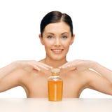 Belle femme avec la bouteille d'huile Image stock