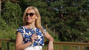 Belle femme avec la camomille blanche sur des pins de fond dans la forêt d'été banque de vidéos