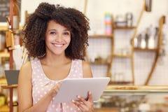 Belle femme avec la coiffure Afro utilisant un comprimé numérique images stock