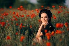 Belle femme avec la couronne de fleur dans un domaine des pavots photo libre de droits