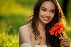 Belle femme avec la fleur de Gerbera appréciant la nature. photos libres de droits