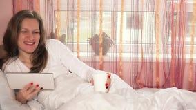 Belle femme avec la tasse et la tablette de café regardant la caméra et le sourire clips vidéos