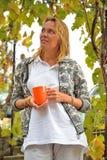 Belle femme avec la tasse orange aux vignes Image libre de droits