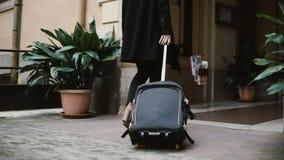 Belle femme avec la valise allant à partir de l'appartement La femme d'affaires avec des bagages vont se déclencher, vacation banque de vidéos
