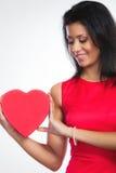 Belle femme avec le boîte-cadeau en forme de coeur rouge Photo stock