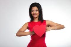 Belle femme avec le boîte-cadeau en forme de coeur rouge Photographie stock