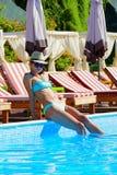 Belle femme avec le chapeau se reposant par la piscine images libres de droits