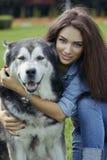 Belle femme avec le chien de Malamute Photo stock