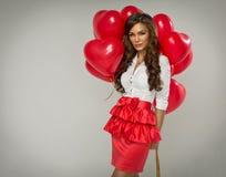 Belle femme avec le coeur rouge de ballon Photos stock