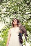 Belle femme avec le faucon sur la fleur Photos stock
