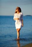 Belle femme avec le jus d'orange à disposition dans des vêtements blancs sur la plage Photographie stock libre de droits