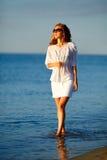 Belle femme avec le jus d'orange à disposition sur la plage au lever de soleil Image libre de droits